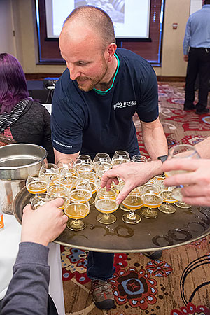 Jeremy serving an enormous tray of beers at a seminar.